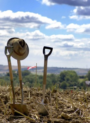 Photograph of three spades stuck upright in the ground, against a blue sky and rolling fields in the background. Phil Harding's hat hang's on one of the spade handles.