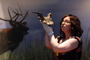 Curator of Archaeology Natalie McCaul holding the deer headdress.
