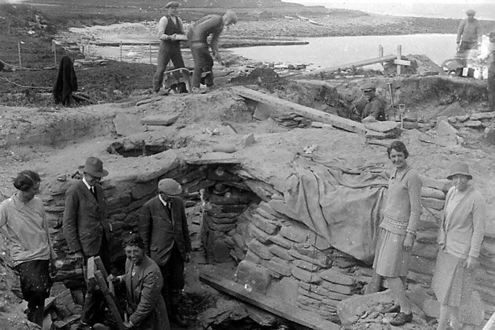 "Black and white photograph from around 1930, showing two women standing within/at the edge of an archaeological trench, while four other people stand in the trench base. The caption reads ""Margaret Simpson (on the far right of the picture) at Gordon Childe's excavations at Skara Brae in about 1930."""