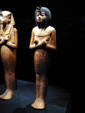 A wooden shabti with an ebony wig, bronze uraeus, and gold collar
