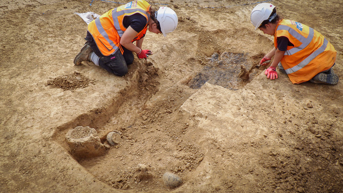 Two archaeologists excavating the grave