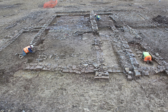 Three archaeologists excavating within the remains of the stone walls of the rectangular building