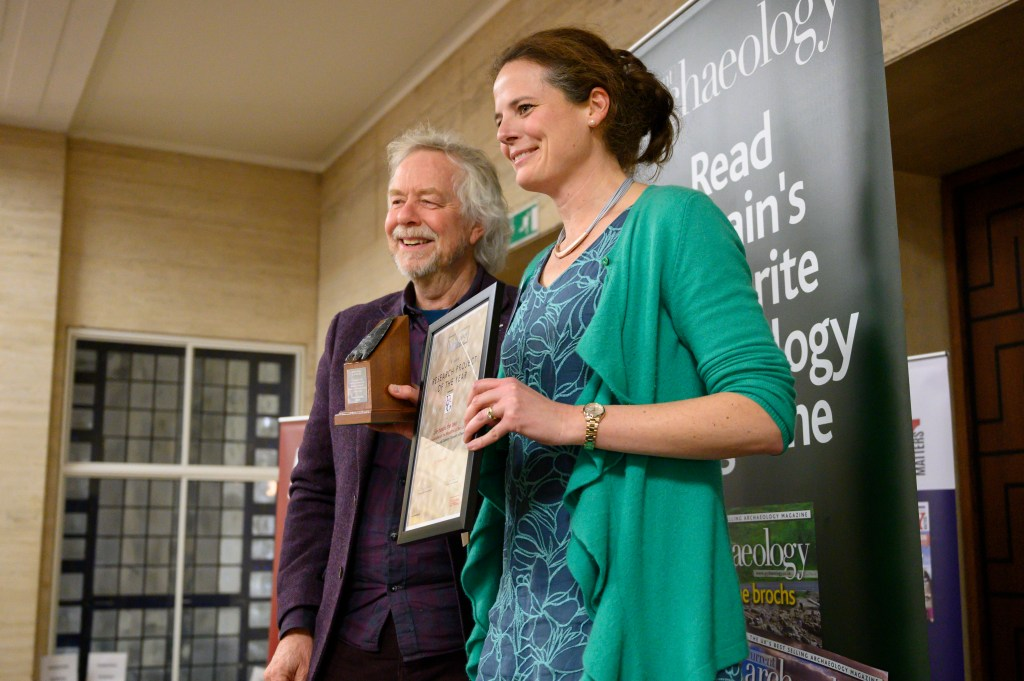Julian Richards, who presented the Current Archaeology Awards, on stage with Nicky Milner from the University of York as she collects the 2020 Research Project of the Year award for the work done at the Mesolithic site of Star Carr.