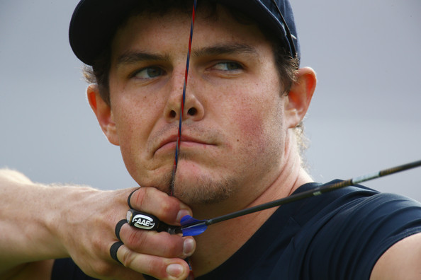 Olympic silver medalist Jake Kaminski demonstrates the proper split-finger hook: one finger above the arrow and two fingers below it, with emphasis on correct finger placement on the string.