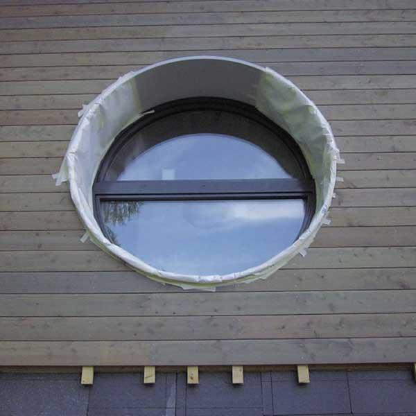 fenêtre ronde dans une maison en bois