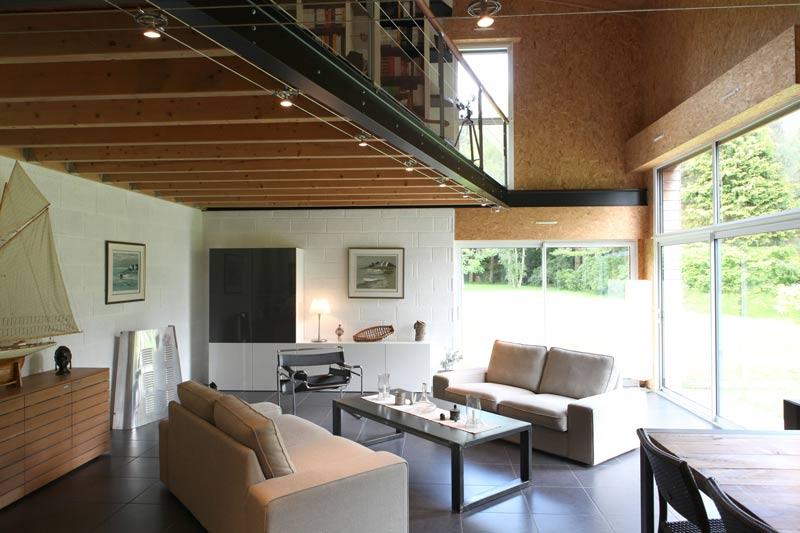 séjour confortable avec grandes fenêtres et galerie en bois