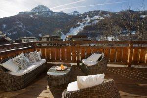 terrasse en bois d'un chalet enneigée avec vue vers les montagnes