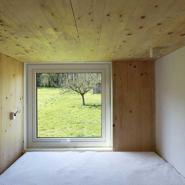 chambre à coucher avec fenêtre d'une maison bois