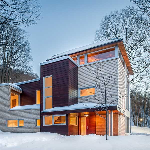 Une maison de montagne en bois dans la poudreuse au Canada