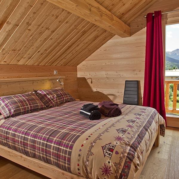 chambre des parents en bois dans maison bois en Hautes-Alpes