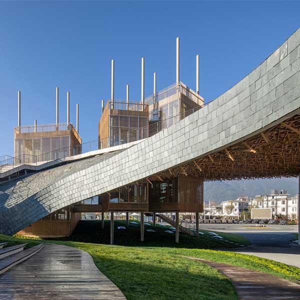 Le toit ondulé en bois et ardoise du Performing Arts Center, à Dali, en Chine, abrite des jardins © Jin Weiqi