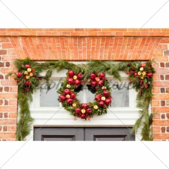 Traditional design of a christmas wreath attached to the front of classic home