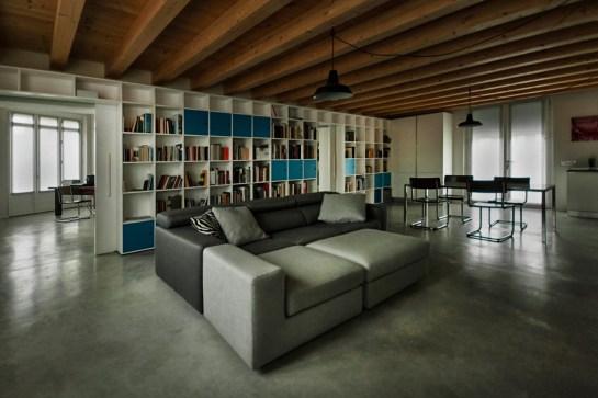 L'ampia libreria divide 2 ambienti distinti, tra la zona Living e lo Studio. Dettagli: Pavimento in cemento tirato ad elicottero, effetto biliardo.