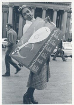 Woman posing with Early Music Month sign Credit: Boston 200 records, Collection # 0279.001, Photographs, Boston City Archives, Boston
