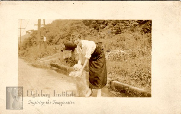 In this undated real photo postcard, a woman plays with her dog on a road. It was printed by the Prager's Studio and Frame Shop of Wheeling, WV. From the Ellen Dunable Postcard Collection of the Museums of Oglebay Institute.