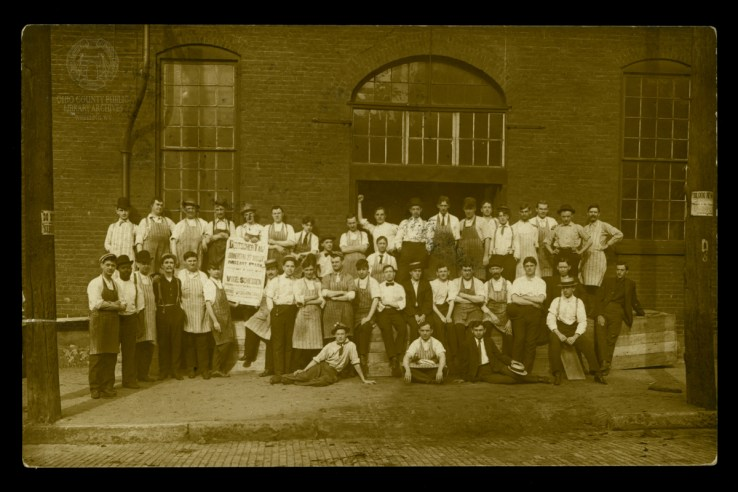 Workers at an unidentified business display a sign for German Day at Mozart Park in this 1908 real photo postcard. Ohio County Public Library Archives.