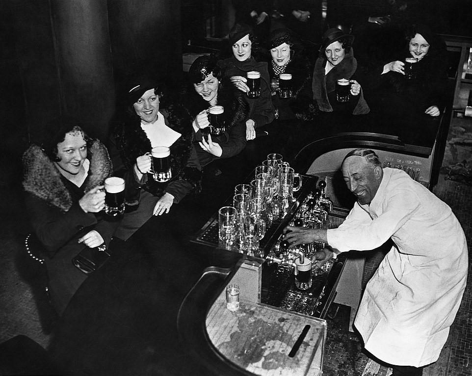 Un grupo de mujeres y el camarero sonríen mientras beben cerveza tras la abolición de la 18ª enmienda (1933).