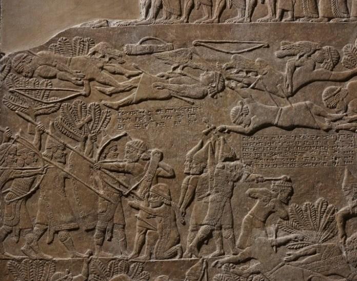 Fig. 12.2. Detalle del panel B (gif. 12) en el que se aprecian varias inscripciones que narran los acontecimientos del rey Teuman y su sucesor. Se puede apreciar como al sucesor un soldado asirio le golpea con una maza en la cabeza; en la parte superior los cadáveres de los elamitas caídos y como estos están siendo devorados por cuervos. Fuente: British Museum. Neoasirio