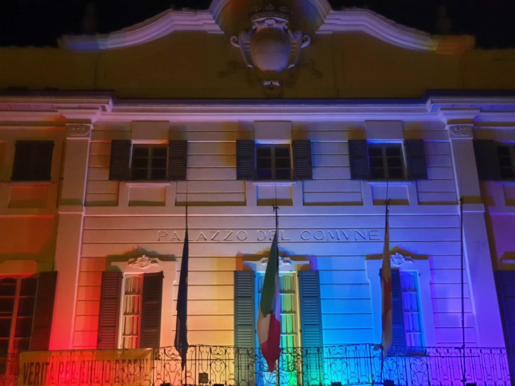 Foto di Palazzo Estense, sede del Comune di Varese, con un fascio di luce proiettato verso l'alto raffigurante i colori della bandiera arcobaleno.