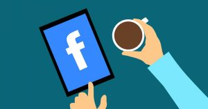 Facebook logo on ipad with hand holding coffee cup