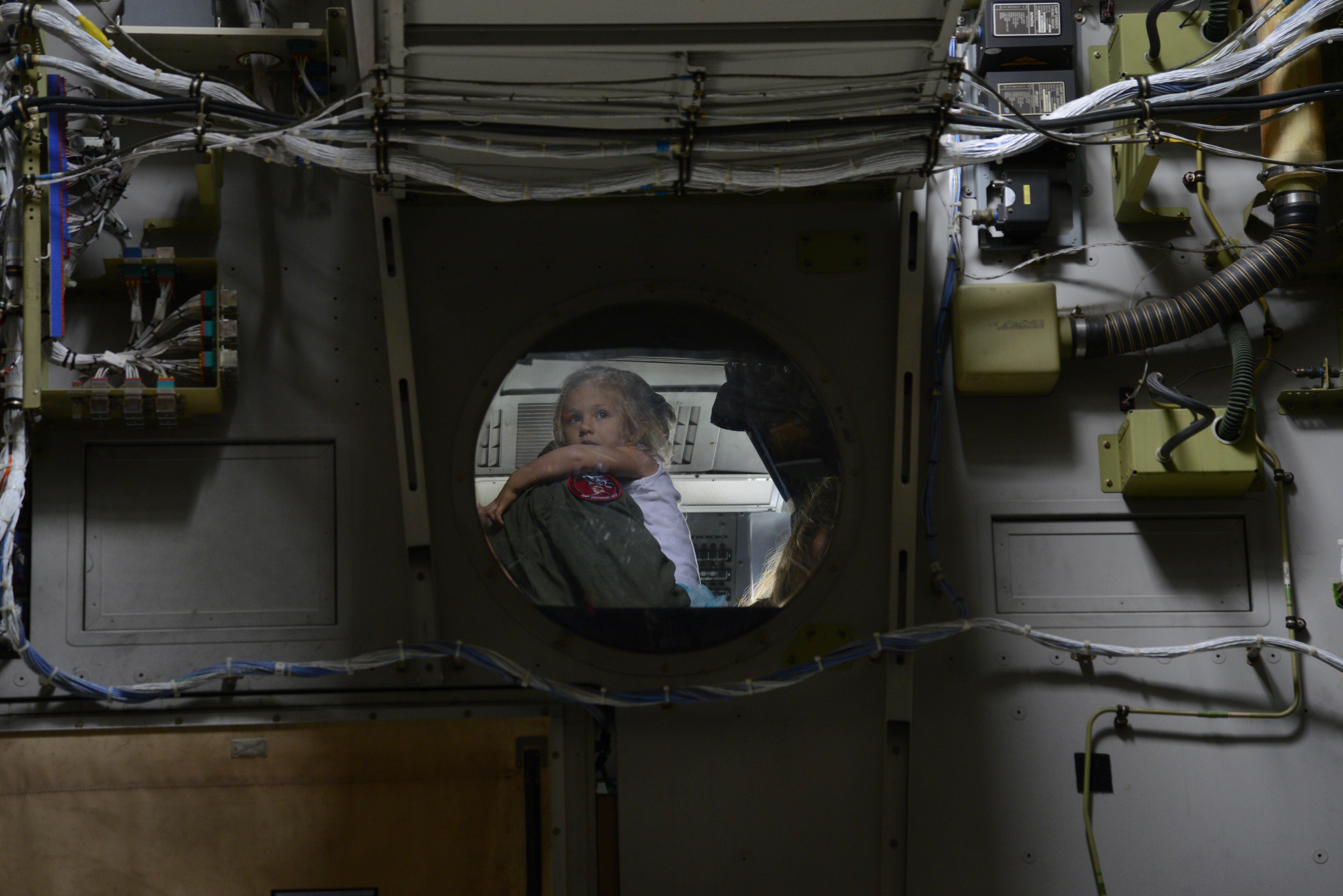 A child looks down from the cockpit of a C-17 Globemaster III during the Special Needs Day of Arctic Thunder Open House at Joint Base Elmendorf-Richardson, Alaska, July 29, 2016. The Arctic Thunder Open House is a biennial event hosted by JBER and is historically the largest two-day event in the state and one of the premier aerial demonstrations in the world. The event features more than 40 key performers and ground acts to include the JBER joint forces, U.S. Air Force F-22, and U.S. Navy Blue Angels demonstrations teams, July 30-31.  (U.S. Air Force photo by Airman 1st Class Valerie Monroy)