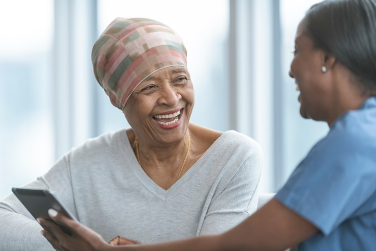 A older woman having a discussion with a nurse.