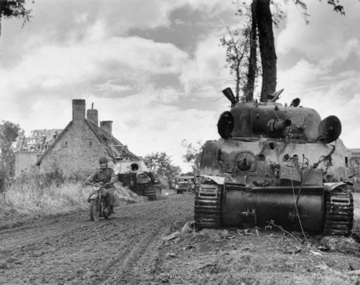 A motorcycle despatch rider passes a knocked-out Sherman tank and behind, a German Panther at Fontenay-le-Pesnel, 27 June 1944.