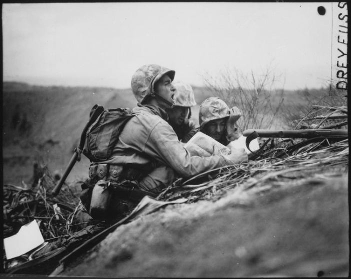 Observer who spotted a machine gun nest finds its location on a map so they can send the information to artillery or mortars to wipe out the position. Iwo Jima, February 1945.