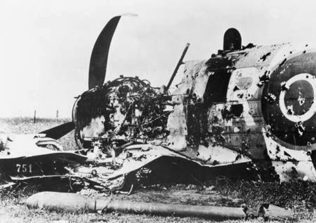 A shot-down Hawker Typhoon IB of 245 squadron RAF. The fuselage shows extensive flak damage and some blackening from fire. The aircraft still bears its invasion stripes from the D-Day landings and in the foreground is a 3 and a quarter inch (60 pound) rocket