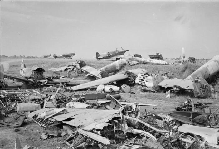 Salerno, 9 September 1943 (Operation Avalanche): Supermarine Spitfires manned by American pilots lined up ready for action on an airfield near Salerno littered with the wreckage of enemy aircraft and aircraft parts. The enemy aircraft were destroyed in Allied bombing attacks on the airfield.