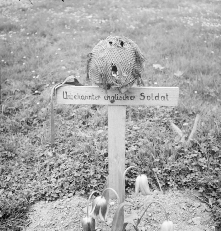 "The grave of a British airborne soldier killed during the battle of Arnhem in September 1944, photographed by liberating forces on 15 April 1945. On the cross is written in German ""Unknown British soldier""."