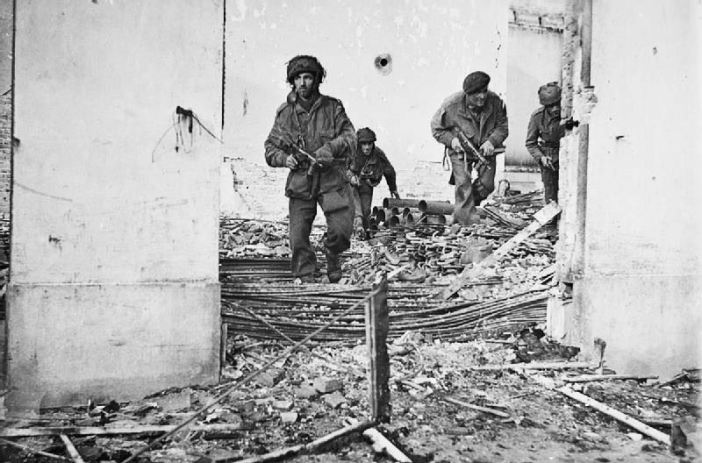Four British paratroopers moving through a shell-damaged house in Oosterbeek to which they had retreated after being driven out of Arnhem.