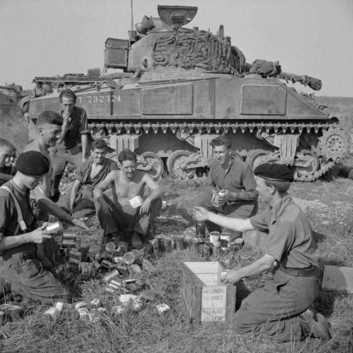 The crew of a Sherman tank of 1st Northamptonshire Yeomanry receive rations before the start of Operation 'Totalise', in August 1944.
