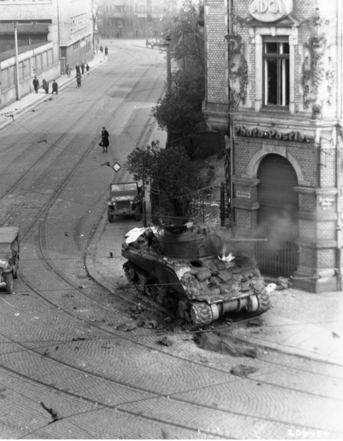 M4 tank of Sgt. George K. Cuthbert, Jr., Company C, 741st Tank Battalion, burns at the intersection of Karl Heine Str. and Zschochersche Str., Leipzig, Germany, 18 April 1945.