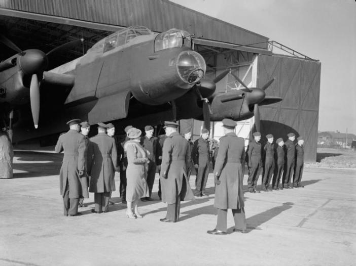 King George VI and Queen Elizabeth visited three Pathfinder stations on 10 February 1944. Here they are seen talking to ground crew of No 156 Squadron at Warboys, Huntingdonshire, beneath the imposing bulk of one of the squadron's Lancasters protruding from a T2 hangar.