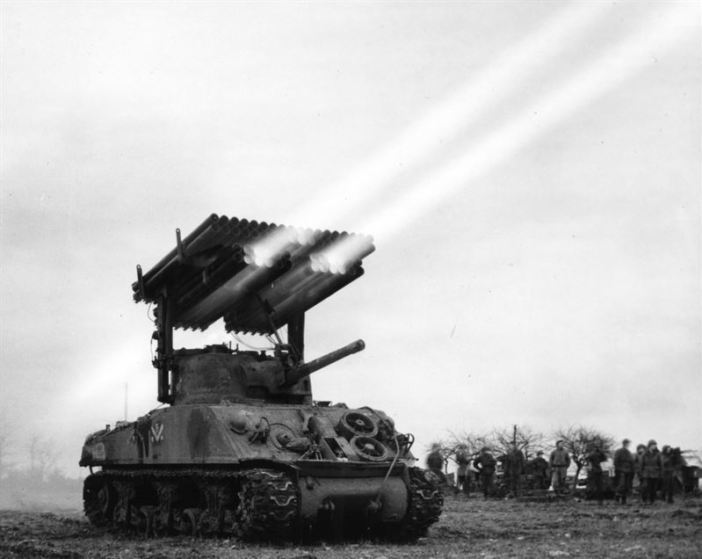 "Firing 4.5 inch rockets from M4-Sherman ""Calliope"" multiple rocket launcher, mounted on M-4, No. A-3 tank. 14th Armored, France."
