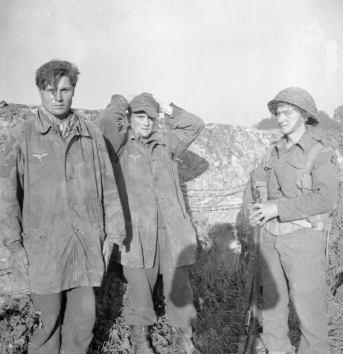 A soldier of 3rd Division guards two German soldiers captured at Caen, 11 July 1944.