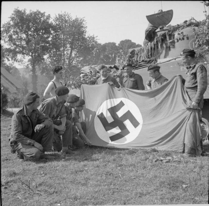 The crew of a Sherman tank of 7th Armoured Division pose with a German swastika flag captured near Roucamps, 8 August 1944.