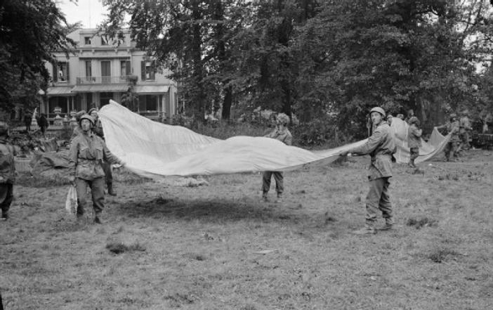 1st Airborne soldiers use parachutes to signal to Allied supply aircraft from the grounds of 1st Airborne Division's HQ at the Hartenstein Hotel in Oosterbeek, Arnhem, 23 September 1944.