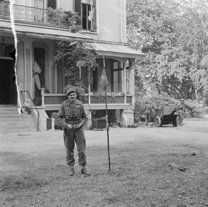 Major-General Roy Urquhart DSO and Bar (leader of the 1st British Airborne Division during the Arnhem Operation) plants the Airborne flag outside his headquarters (Hotel Hartenstein), the last British stronghold in the Arnhem area before the evacuation.
