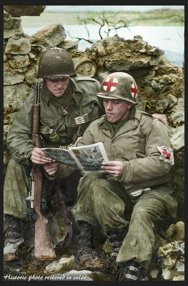 An American Medic and a GI of the US. 80th Infantry Division reading a comic at Reisdorf in Luxembourg near the German Border. 12th of February 1945 Left to right : Pfc Reynold H. Bush Middletown, Ohio , and Pfc Aurelio Maltese, New York