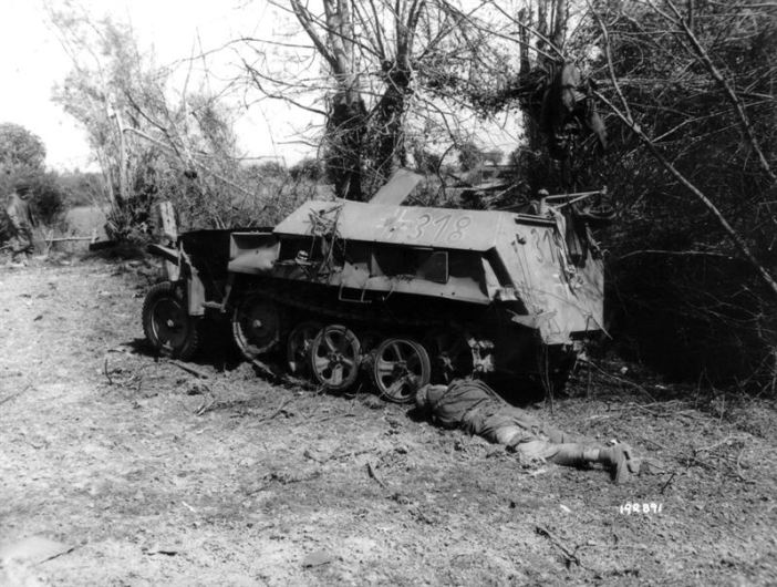 """Aftermath of bombardment of Mortain in front of the station of Mortain-Le-Neufbourg, in the foreground a half-track vehicle Sdkfz of the 2.SS-Panzer division """"Das Reich"""", in the foreground the corpse of a dead German soldier."""