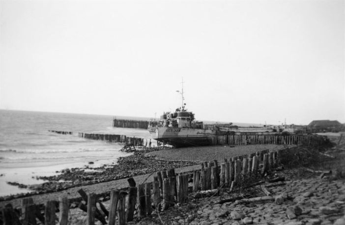 The image shows a wrecked landing craft on the beach of Walcheren.