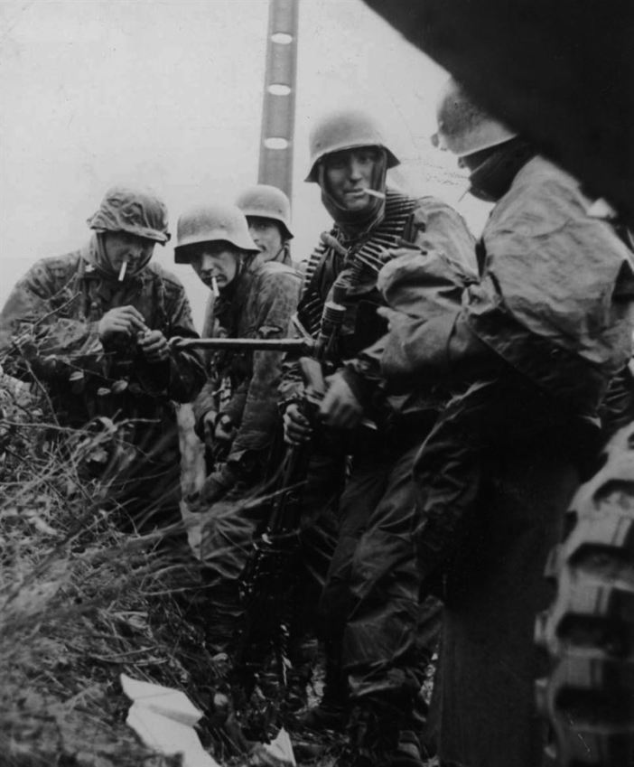 Panzergrenadiers from Kampfgruppe Hansen (one of the three large kampfgruppe of the Leibstandarte Division) take a cigarette brake. Such a state was the norm during combat operations. This photograph was taken after the action on the Poteau and Recht road, in early hours of 18 December 1944.
