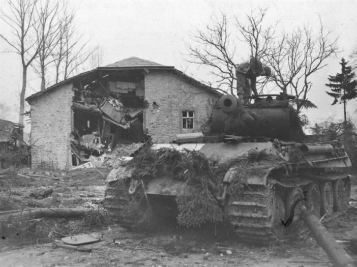 "On Christmas Eve 1944, the 2nd SS Panzer Division Das Reich swept through Manhay and into Grandmenil, pushing aside US Task Force Kane from the 3rd Armoured Division. However, after being pummeled by air strikes on 26 December, the town was assaulted by Task Force McGeorge of the 3rd Armoured Division and taken in the early-morning hours of the 27 by the paratroopers of the 517th Parachute Infantry. This was one of the ""Das Reich"" Panthers lost in the fighting. It is being inspected by a GI from the 3rd Company, 289 Infantry, 75th Division, which occupied the town on 30 December."