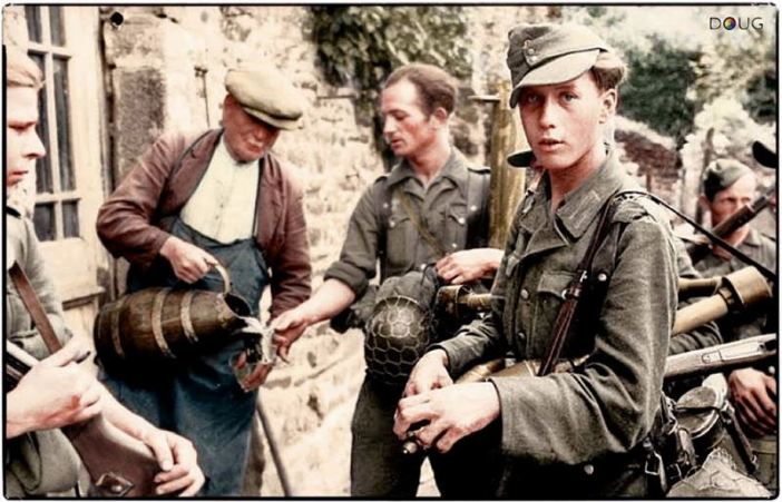 German troops, accepting a drink from a French villager somewhere in Normandy. Mid. June 1944, after the commencement of the allied invasion.