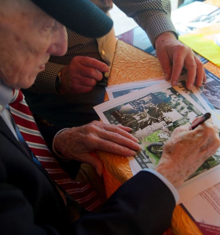 "James ""Pee Wee"" Martin signs a then-and-now picture collage of Erich Bessoir June 7, 2014, at Omaha Beach, in Normandy, France. Bessoir was a German World War II veteran of the Waffen-SS and motorcycle reconnaissance driver. The two war witnesses met to promote international friendships and understanding during the celebration of the 70th anniversary of D-Day. (Credits: Alexander W. Riedel)"