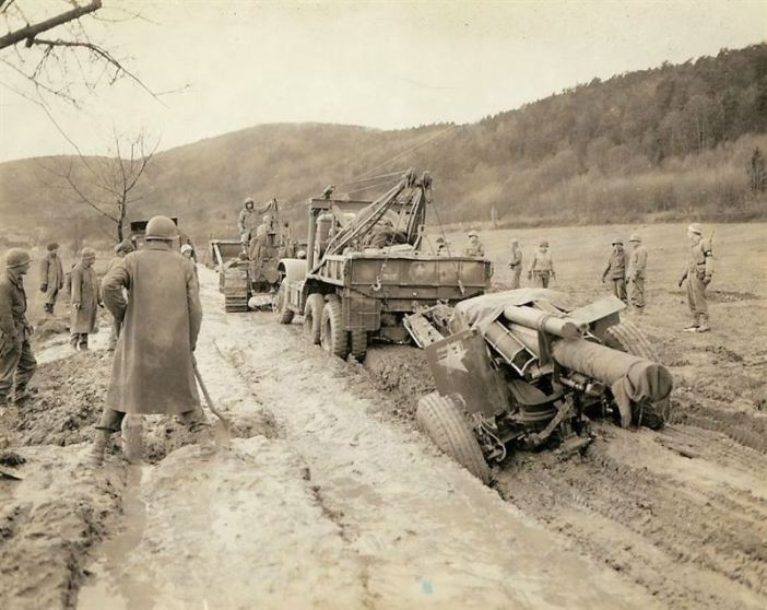 When this wrecker towing a 155mm Howitzer became stuck in the mud in a road, nothing less than a Bulldozer could budge it.