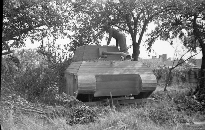 An officer inspects a German dummy tank made of wood, 31 July 1944. (Credits: © IWM (B 8296))