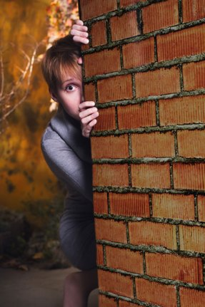 woman-hiding-behind-wall